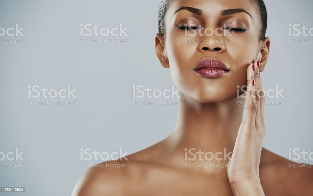 Serene woman with closed eyes and touching cheek stock photo