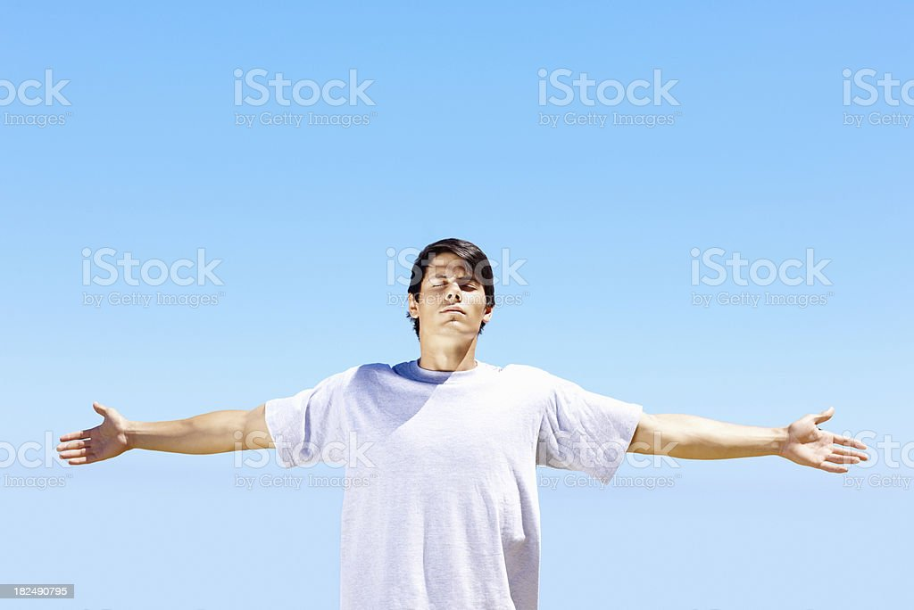 Serene young guy with arms outstretched over blue sky royalty-free stock photo