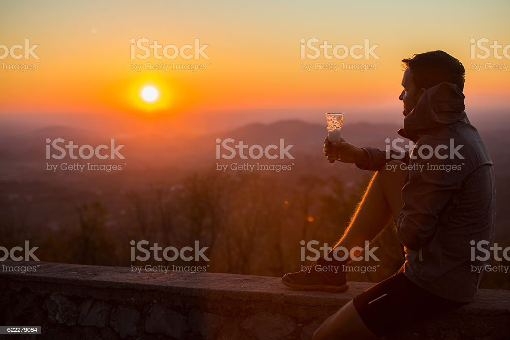 Serene Young Man Enjoying Sunset after Cross-Country Running, Alps, Europe stock photo