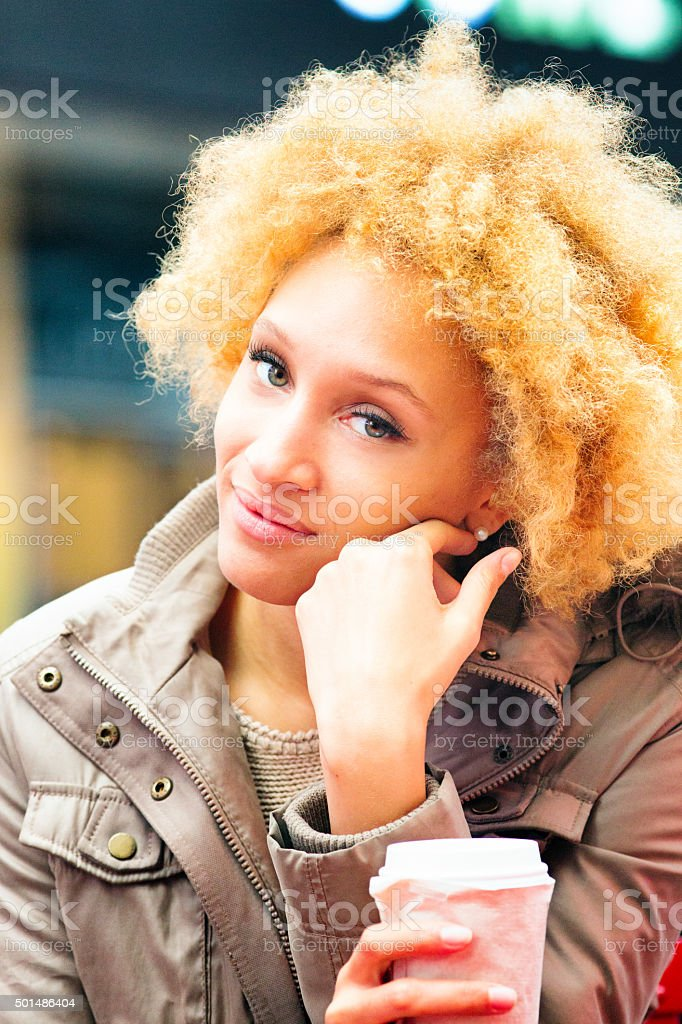 Serene young woman caresses her cheek with back of hand stock photo