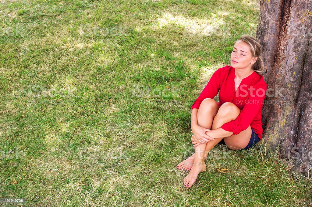 serene young woman enjoying summer freshness under a tree stock photo