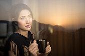 Serene young woman enjoying sunrise view and having coffee break.