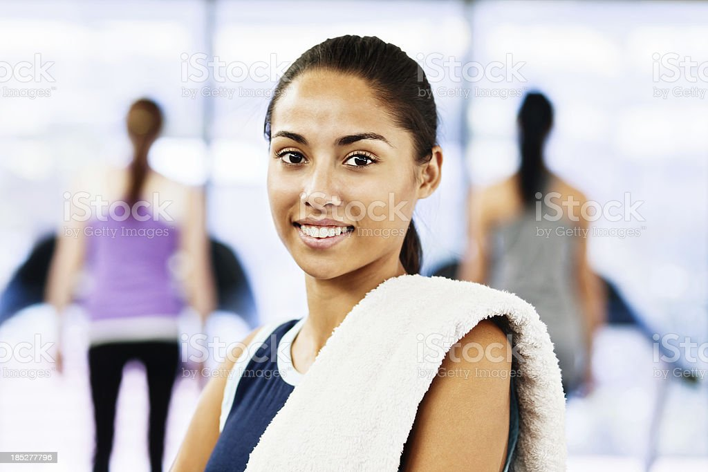 Serenely smiling young woman relaxing after exercise in gym stock photo