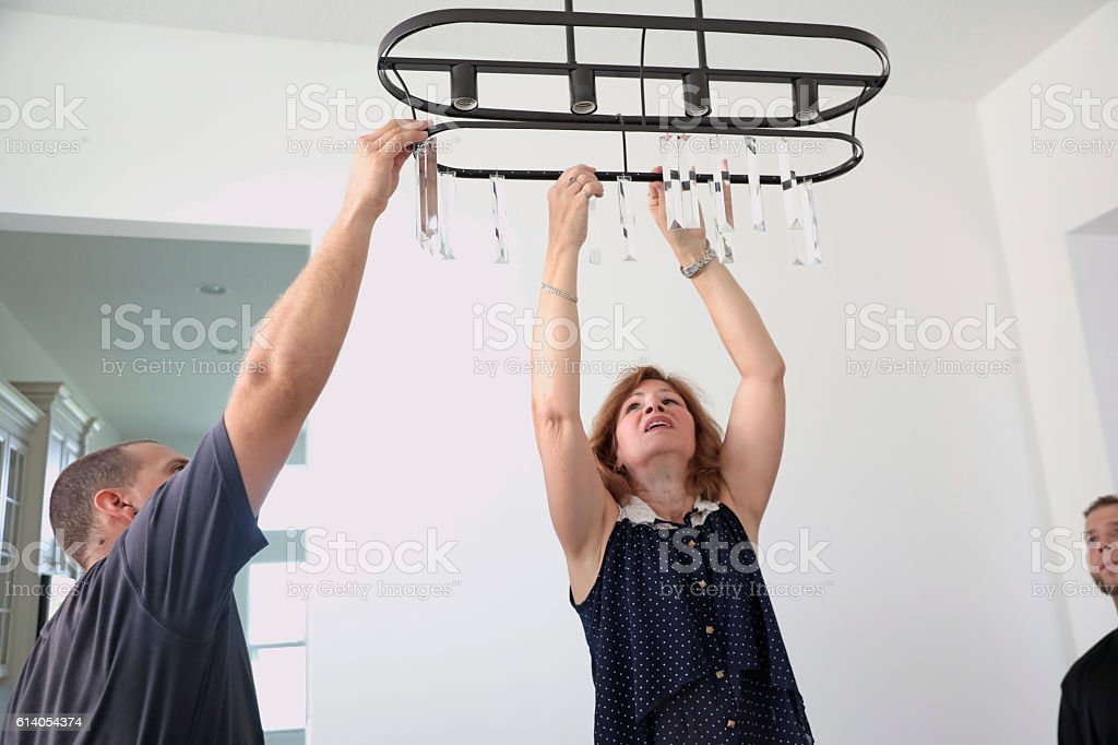 Series: House staging. Professional stagers hanging a crystal light fixture stock photo