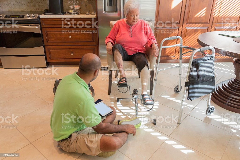 Series: In home physical therapist treating a senior patient stock photo