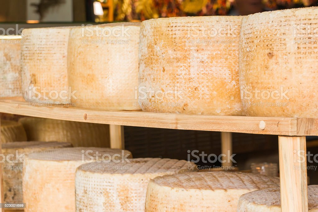series of round forms of cheese for sale in market stock photo