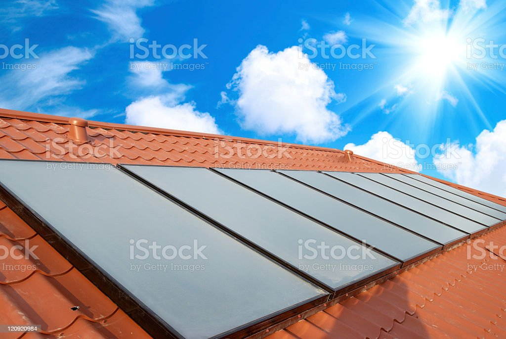 A series of solar panels on a red roof under a blue sky stock photo