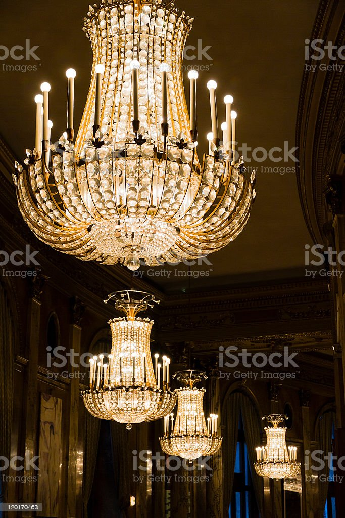 Series of well lit crystal chandeliers stock photo