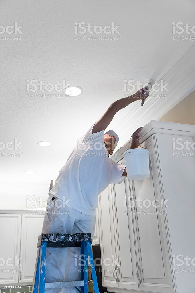 Series- Real Hispanic painter painting ceiling in a kitchen stock photo