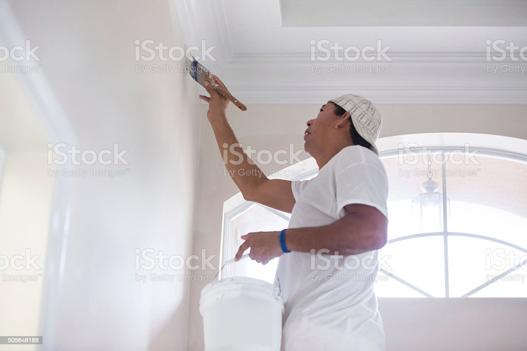 Series- Real Hispanic painter painting wall in home stock photo