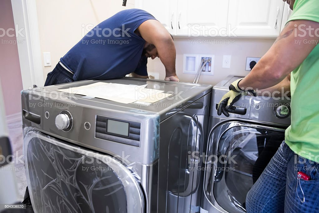 Series- Installing new washing machine and dryer in laundry room stock photo