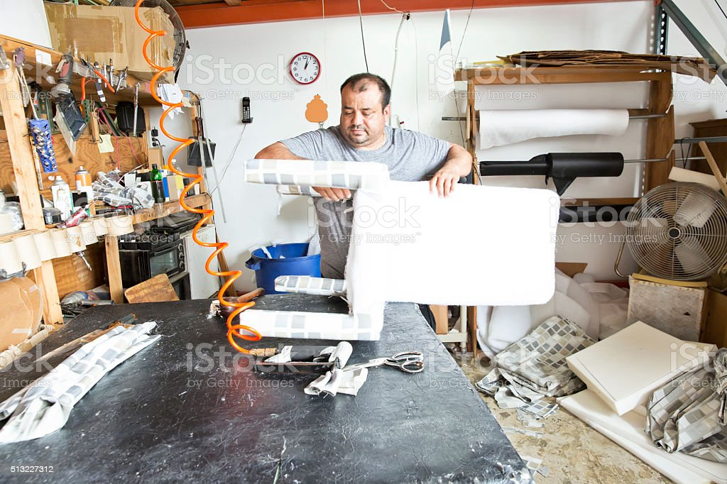 Series- Real Upholstry manufacturer working in his factory stock photo