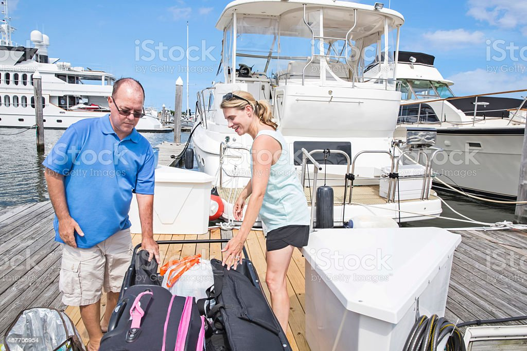 Series: Vacationing Kidney recipient and wife leaving boat with belongings stock photo