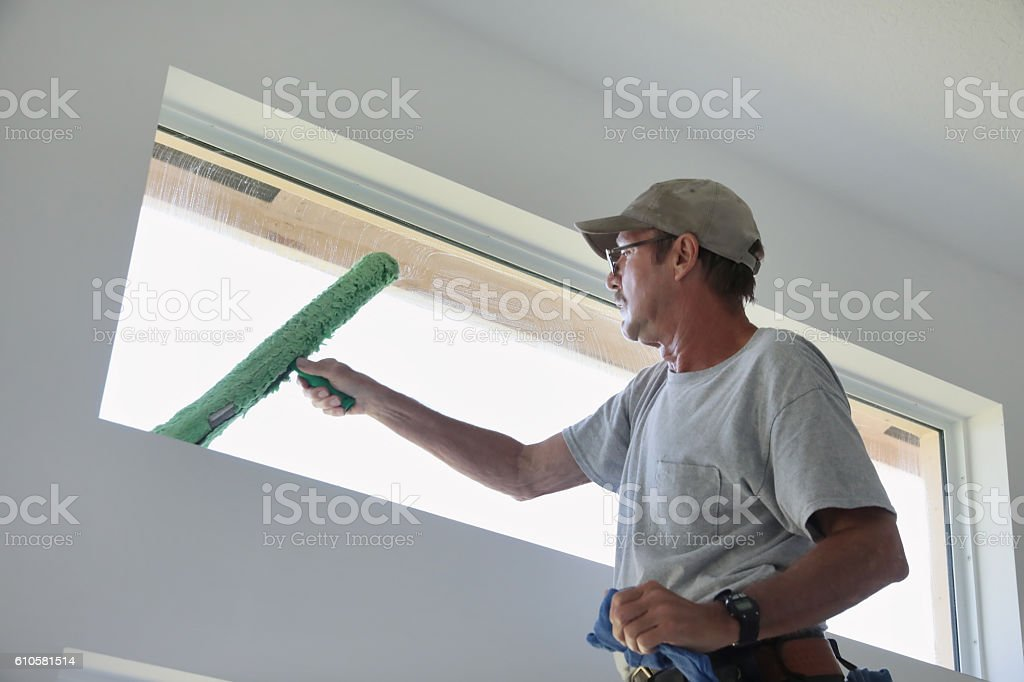 Series: Window washer cleaning inside transom window in a home stock photo