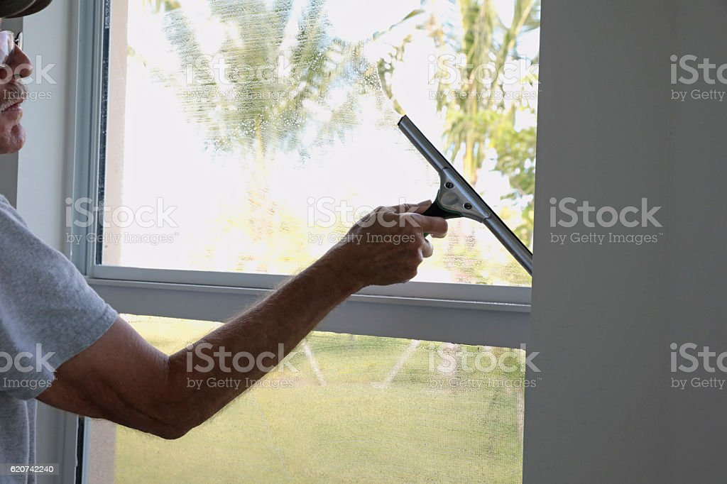 Series: Window washer cleaning the inside window of a home stock photo