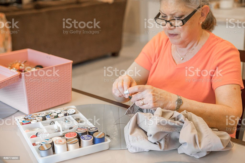 Series:Active senior woman hand sewing a button on pants stock photo