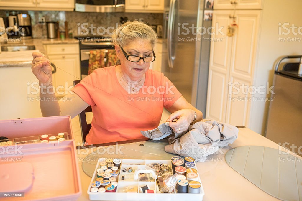 seriesactive senior woman hand sewing at her kitchen table royalty free stock photo. beautiful ideas. Home Design Ideas