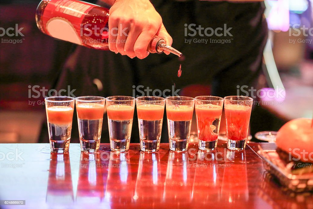 Series:Bartender adding grenadine to a row of fancy vodka shots stock photo