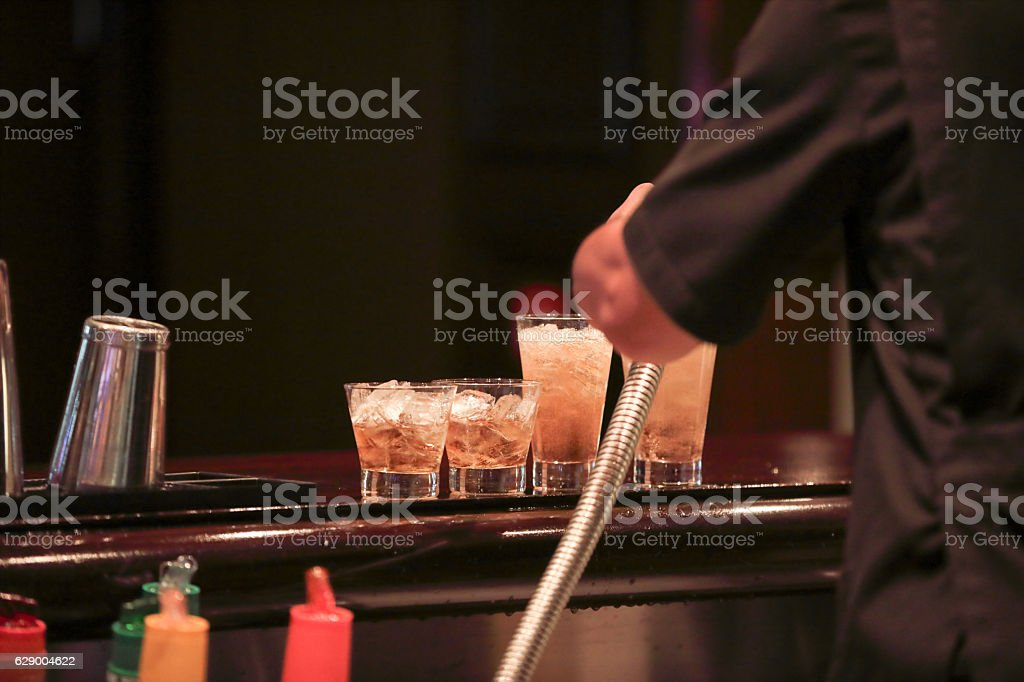 Series:Bartender adding soda water to a mixed cocktails on bar stock photo