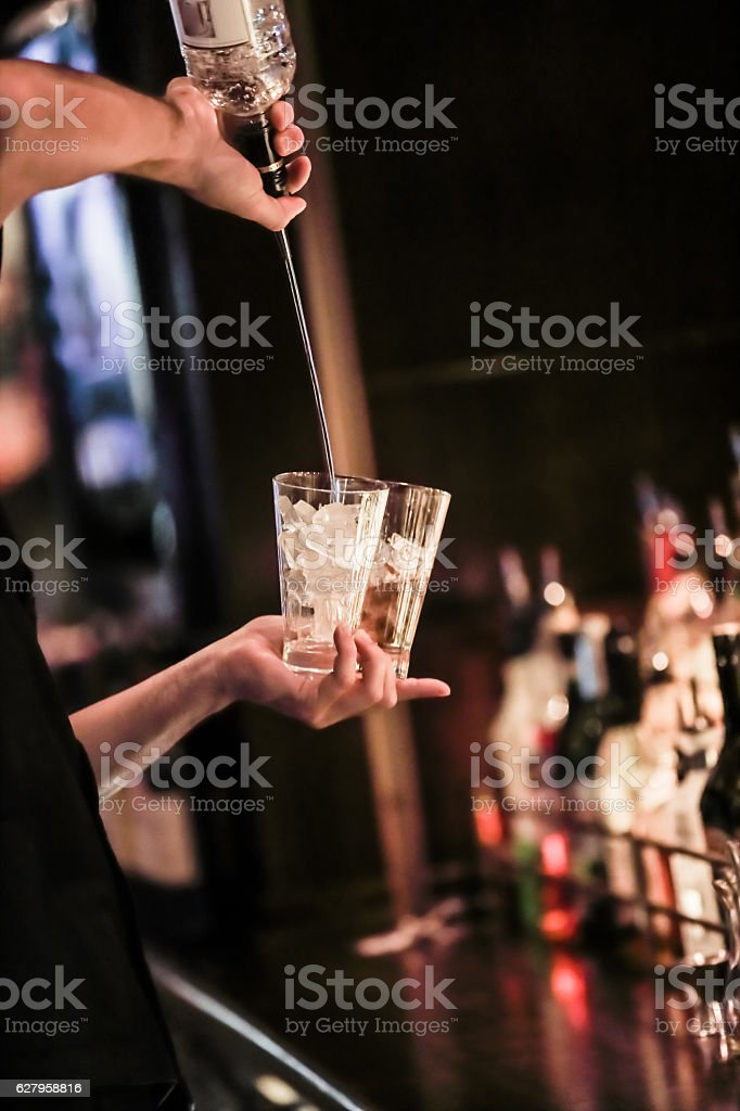 Series:Bartender pours vodka into two glasses filled with ice. stock photo