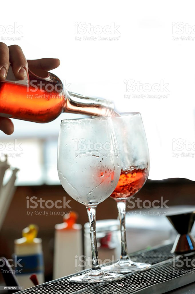 Series:Bartender wine into two chilled glasses stock photo