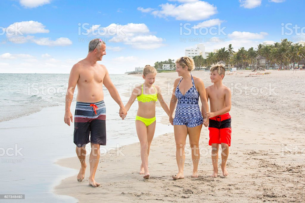 Series:Family talking while walking on the beach holding hands stock photo