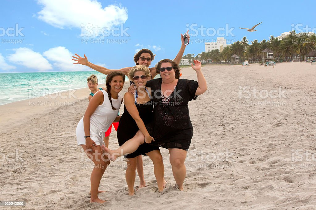 Series:Four women with diverse body shapes having fun at beach stock photo