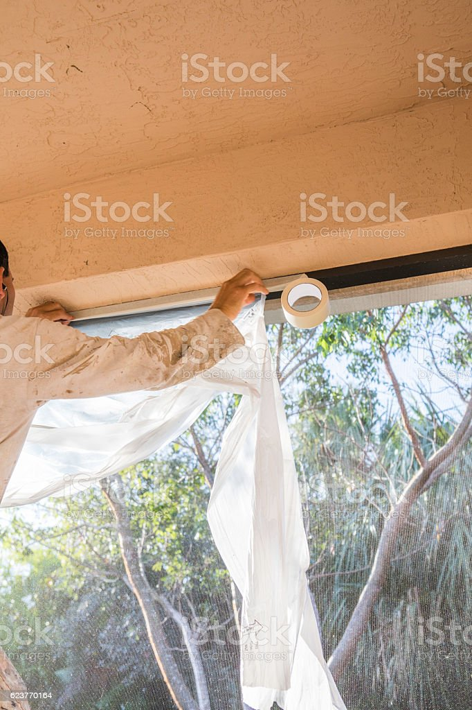 Series:Hispanic house painter prepping home for painting stock photo