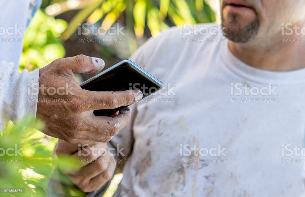 Series:Hispanic painter looking at cell phone with coworker stock photo