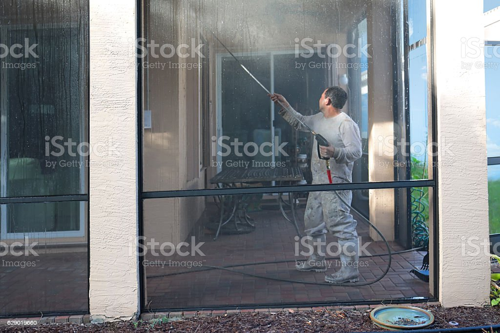 Series:Hispanic worker power washing screened in patio of home stock photo