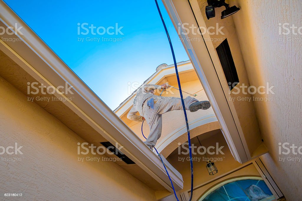 Series:House painter in a dangerous position while painting house stock photo