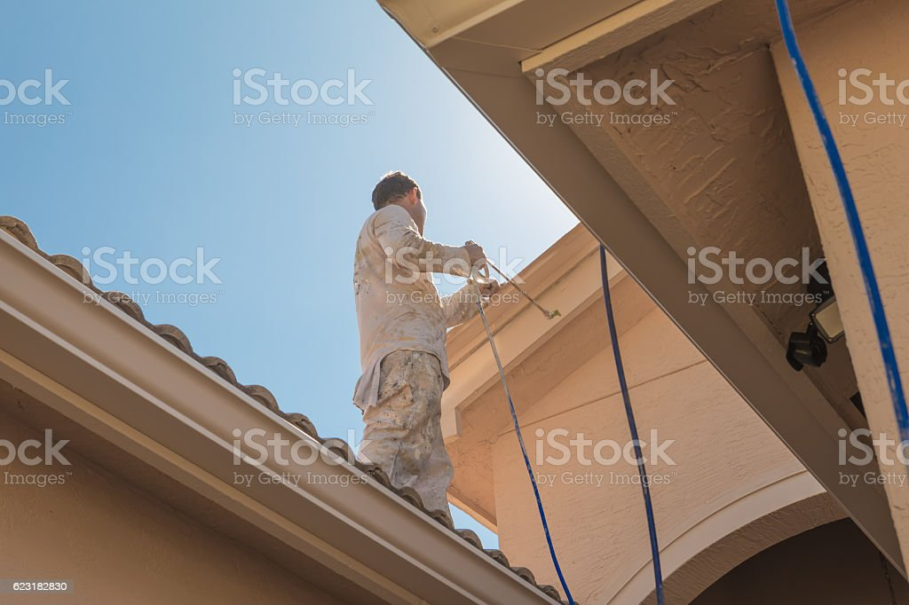 Series:House painter standing on roof spray painting trim stock photo