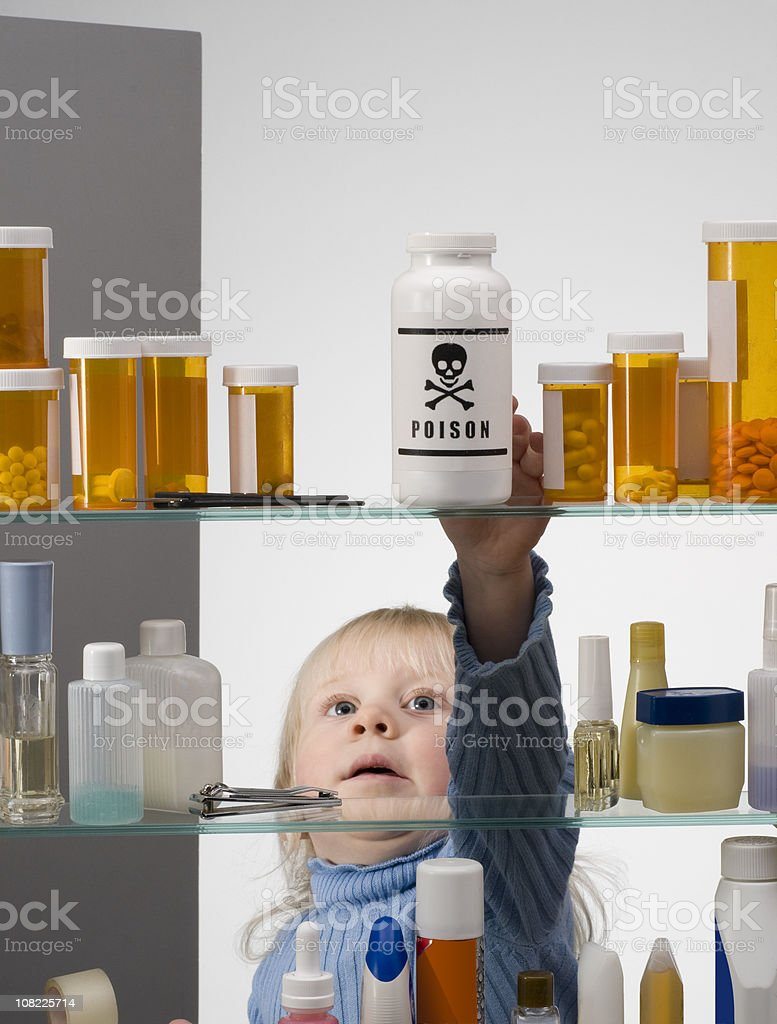 CHILD SAFETY SERIES #1-Little Girl Reaching Into Medicine Cabinet stock photo