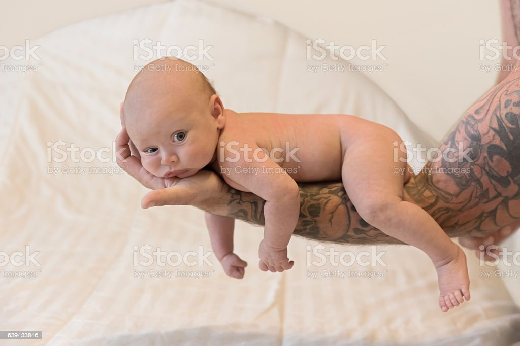 Series:Naked baby boy being held on father's tattooed arm stock photo