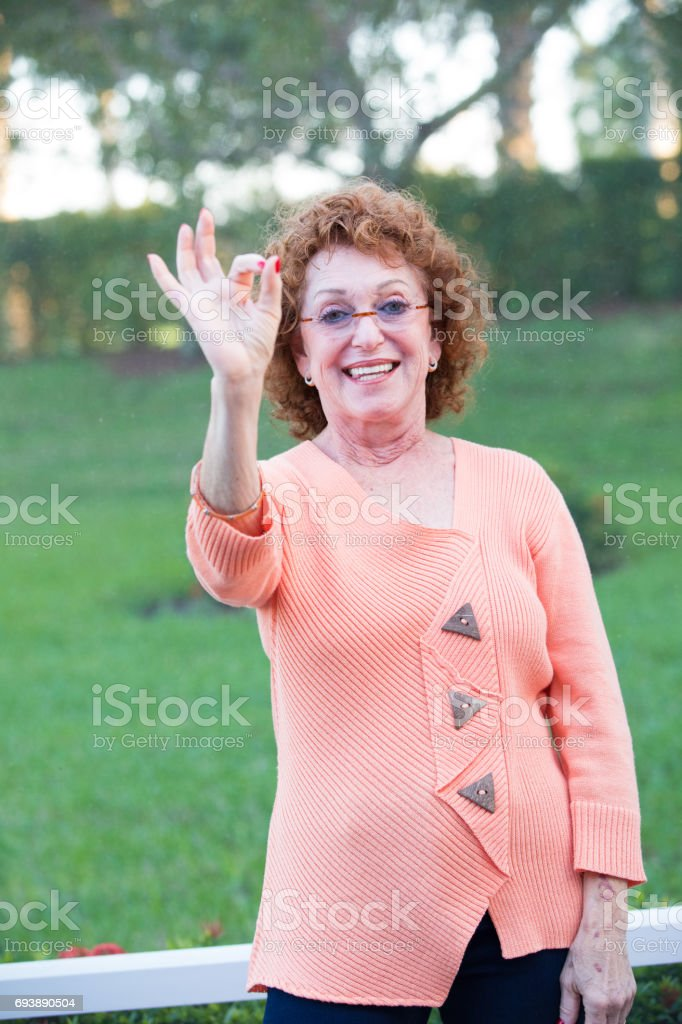 Series:Okay hand gesture from vibrant senior woman stock photo