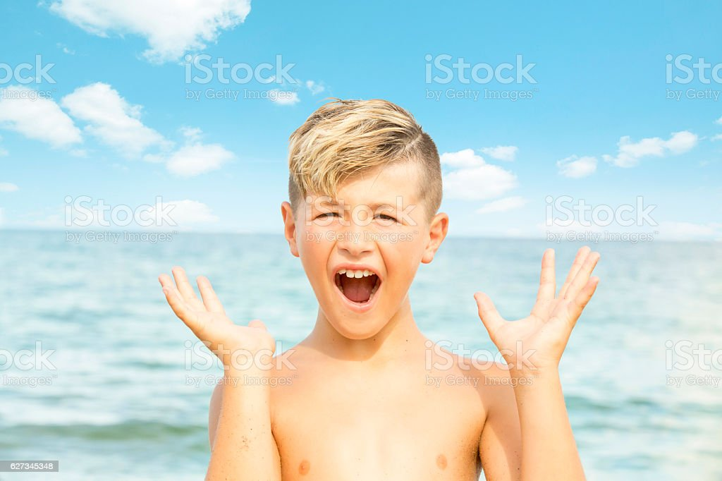 Series:OMG. Blond caucasian boy at ocean with look of excitement stock photo