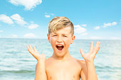 Series:OMG. Blond caucasian boy at ocean with look of excitement