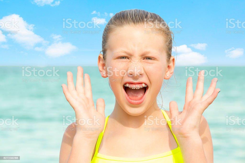 Series:OMG.Tween girl at ocean with look of excitement stock photo