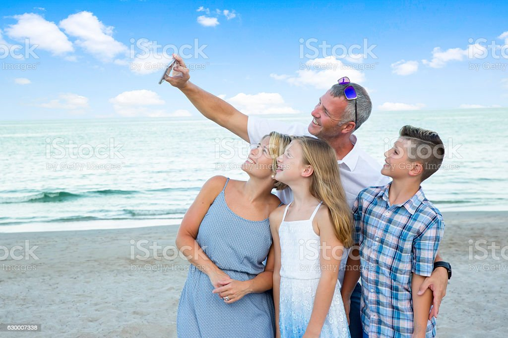 Series:Parents and their two young children taking selfie on beach stock photo