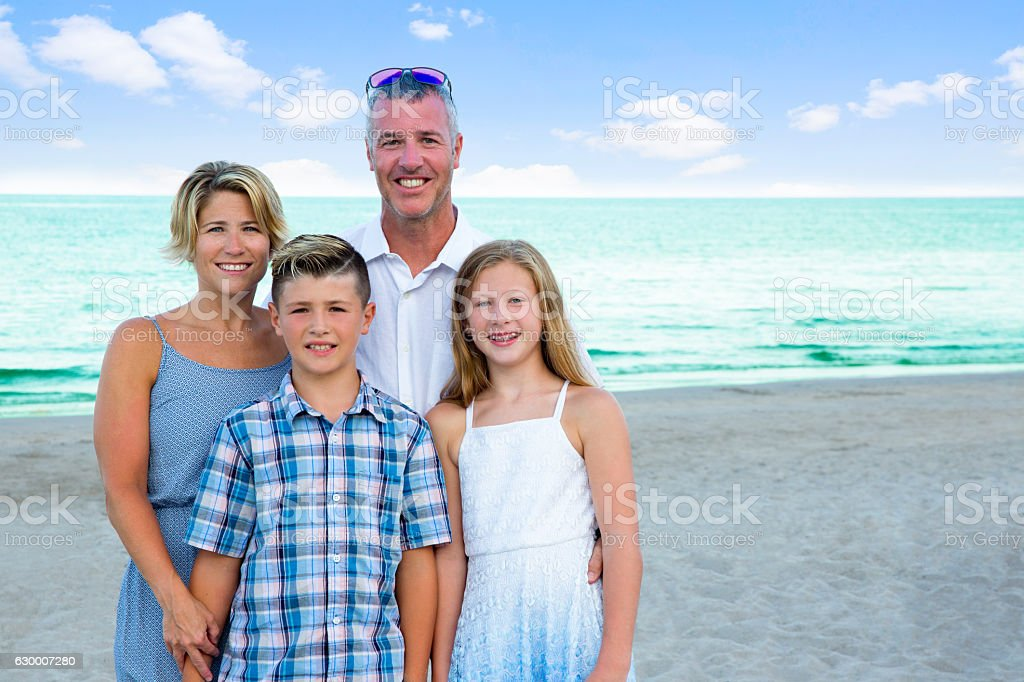 Series:Portrait of real caucasian family of four on beautiful beach stock photo