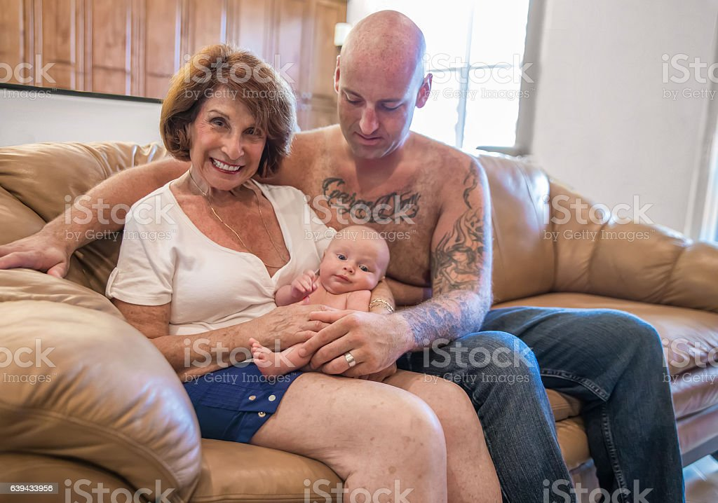 Series:Proud grandmother holds six week old grandson with tattooed father. stock photo