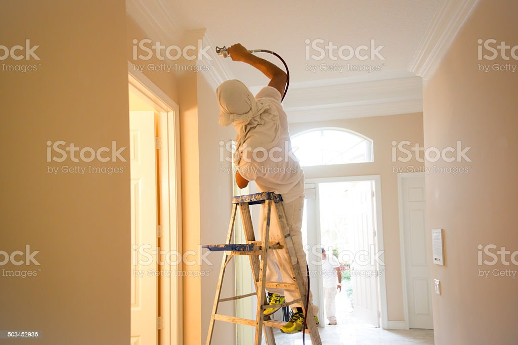 Series-Real painter spraying crown molding in a home stock photo