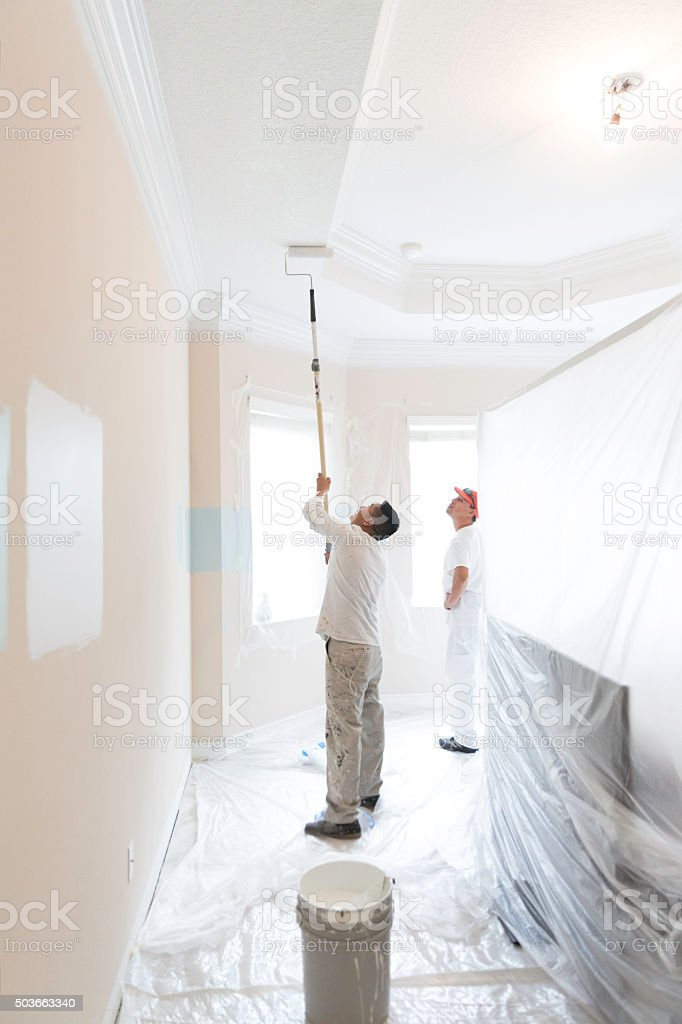 Series-Real painter using paint roller to paint ceiling stock photo
