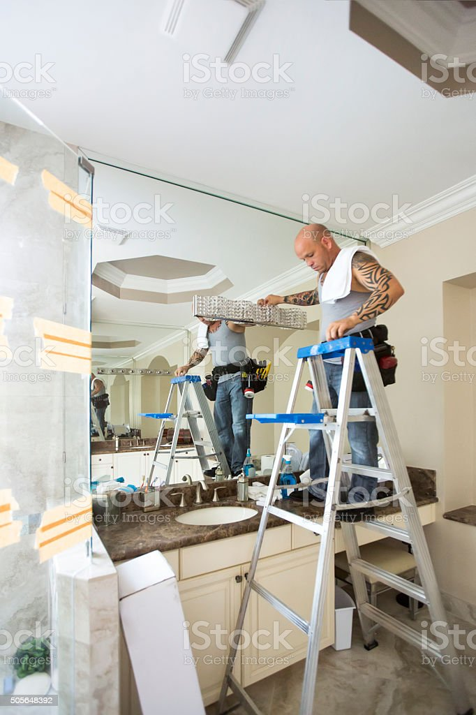 Series-Real tattooed electrician hanging upsacle light fixture in bathroom stock photo