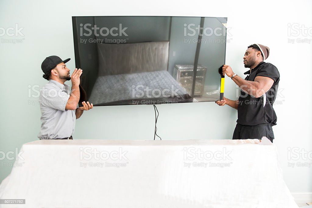 Series-Real televison installers hanging large flat screen TV on wall stock photo