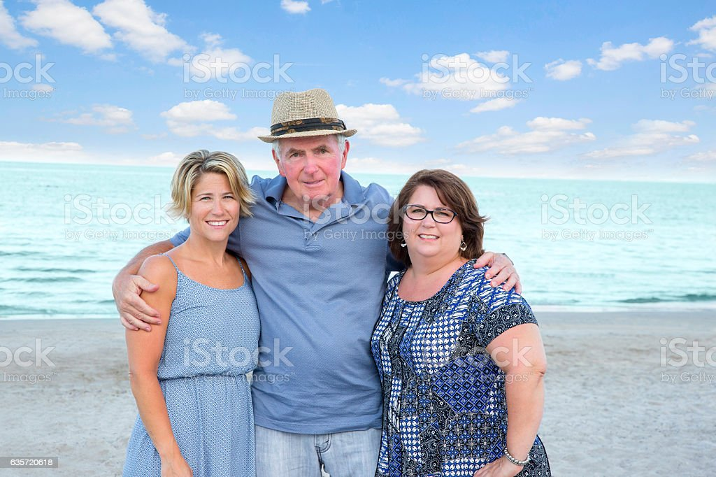 Series:Senior father posing with adult daughters at beach stock photo