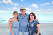 Series:Senior father posing with adult daughters at beach