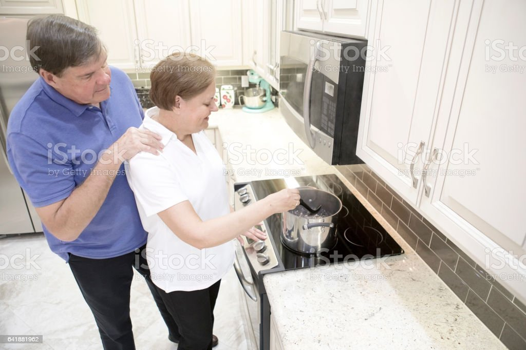 Series:Senior tender moment. Married couple at home cooking at stove stock photo
