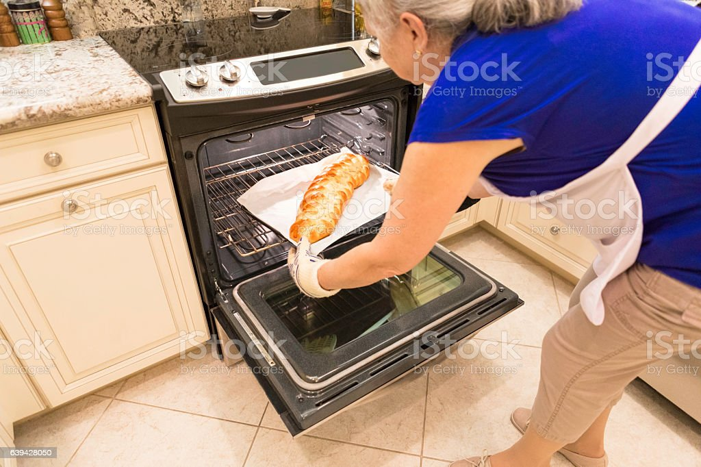 Series:Senior woman taking homemade braided challah out of the oven stock photo
