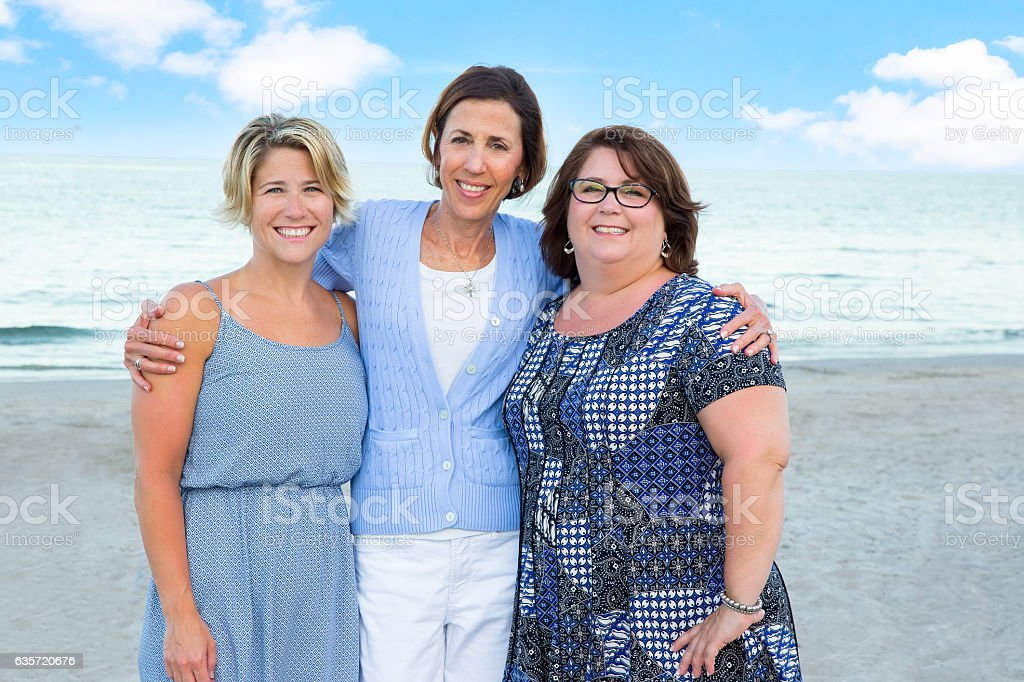Series:Senior youthful mother posing with adult daughters at beach stock photo